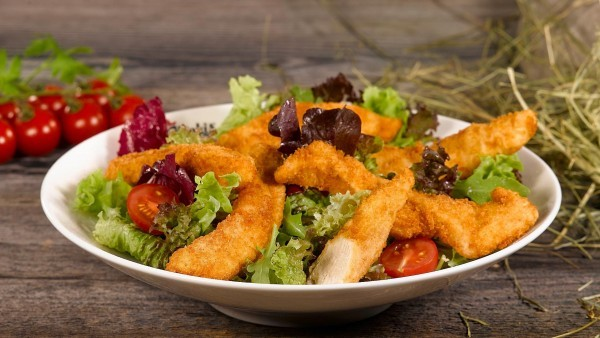 Gebackene Filetstreifen auf buntem Salat